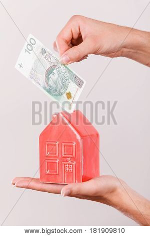 Household savings and finances economy concept. Man putting zlotych money into a piggy bank in the shape of a house studio shot on grey background
