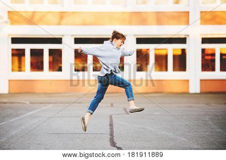 Cute 9 year old kid girl playing on school yard, wearing denim jeans and grey sweatshirt