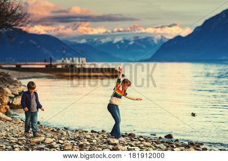 Two happy kids, little brother and big sister, playing together by lake Geneva at sunset with swiss mountains Alps on background. Image taken in Lausanne, Switzerland