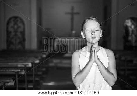 Child praying in church, black and white image