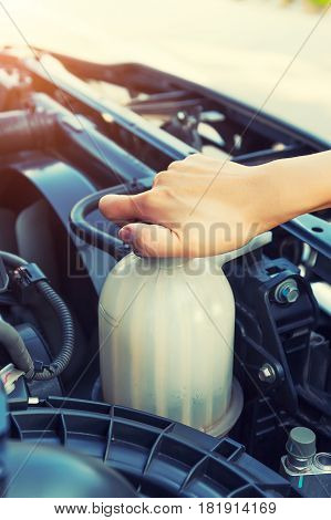 Asian girl checking level of coolant car engine.