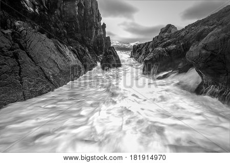 Movement of water on the shores of cold Norwegian Sea at evening time. Lofoten islands. Beautiful Norway landscape. Black-white photo.