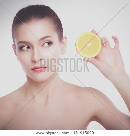 Beautiful young shirtless woman holding piece of orange in front of her eye while standing against white background.