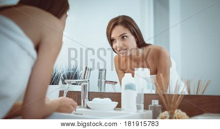 Young woman washing her face with clean water in bathroom.