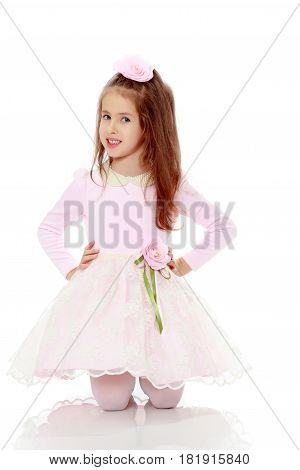 Dressy little girl long blonde hair, beautiful pink dress and a rose in her hair.She poses on the floor on his knees.Isolated on white background.