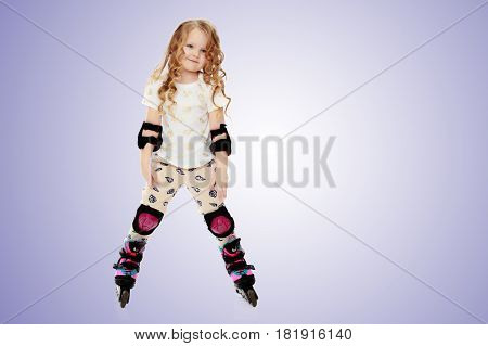 Beautiful, chubby little girl with long, blond, curly hair.Girl riding roller skates in protective gear.Purple gradient background.