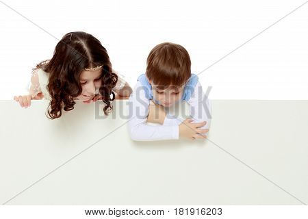 A boy and a girl peeping from behind the white banner.The children look down.Isolated on white background.