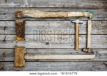 Rusty tools sledgehammer ax and two hammers lie on old boards background with copy space for text top view flat lay time concept