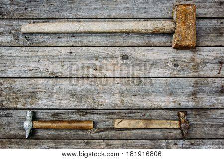 Rusty tools sledgehammer and two hammers lie on old boards background with copy space for text top view flat lay time concept