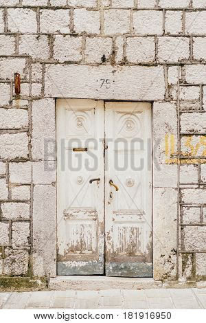 Old white doors. Wood texture. Old shabby, irradiated paint