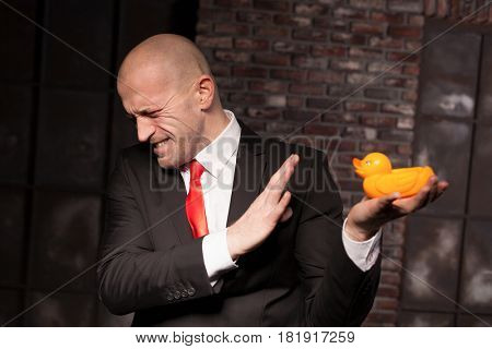 Contract murderer looks at little toy duck in hand