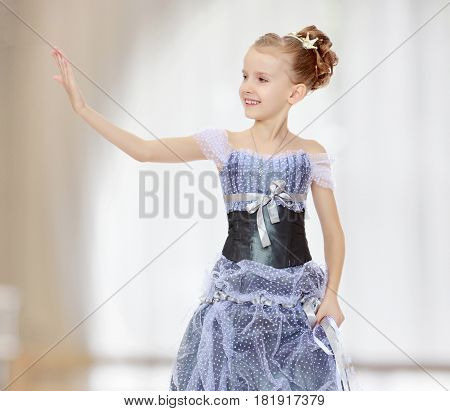 Slender little girl , with beautiful hair on his head, elegant long Princess dress.The girl stares at his palm like a mirror.In a room with a large semi-circular window.