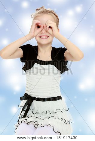 Beautiful little blonde girl dressed in a white short dress with black sleeves and a black belt.The girl folded her palms into a tube in the form of binoculars.Blue Christmas festive background .