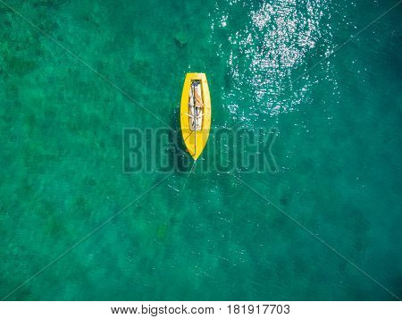 Aerial view of yellow boat floating at the sea.