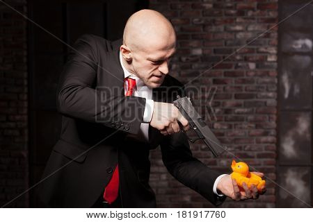 Angry contract murderer aims a pistol on toy duck