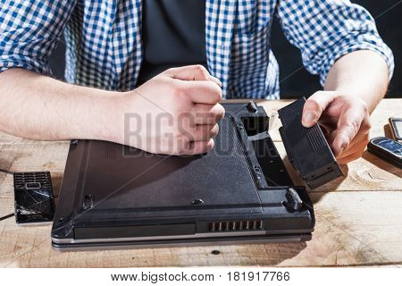 Service engineer disassembling broken laptop