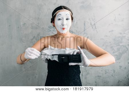 Mime female artist performing with mobile phone