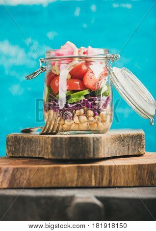 Healthy take-away lunch jar. Vegetable and chickpea sprout vegan salad in glass jar on wooden boards, bright blue wall at background, selective focus. Clean eating, vegetarian, raw, dieting concept
