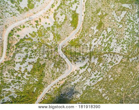 Aerial view of curved roads in mountains.