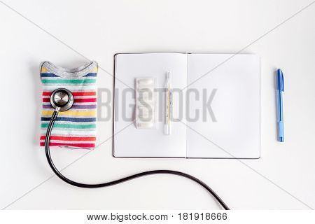 children's doctor work with stethoscope and notebook on white desk background top view mock-up