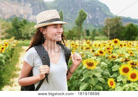 Traveling woman with backpack and straw hat looking sunflower in field