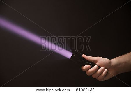 Black Ultraviolet Flashlight In Male's Hand Isolated On Black Background