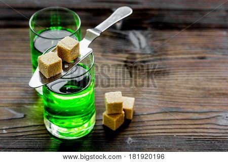 green absinthe in glass with cubes of sugar on wooden table background