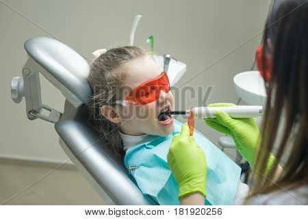 close up view of small girl patient at the dentist. Doctor is making dental fillings with ultraviolet light