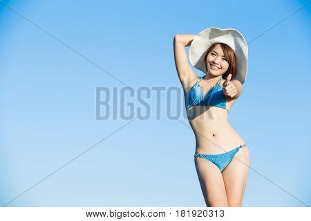 beauty woman wear bikini and thumb up with blue sky