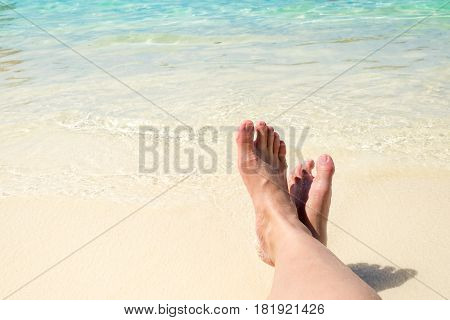 Close Up Traveler Cross Barefoot Leg Laying On Beach At Sea Shore,relaxing In Summer Vacation Time