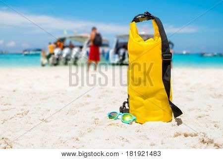Yellow Waterproof Shoulder Bag With Sunglasses On Beach Sand At Sea Shore With Tourist,summer Vacati
