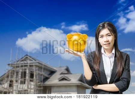 gold piggy bank on hand young asian business woman with house under construction. conceptual image