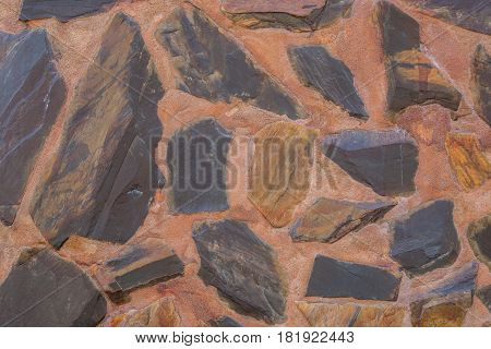 Abstract background wall made of rough stones black and brown