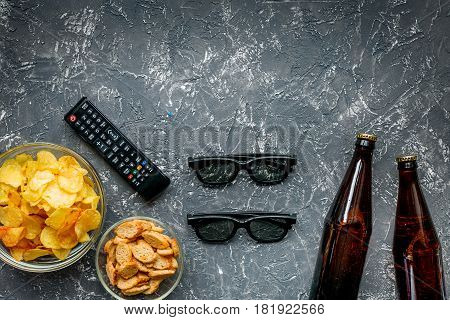 snacks for watching TV film with glasses and control on dark desk background top view mock-up