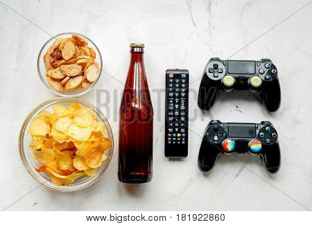 playing video games on console set with chips on white desk background top view mock-up