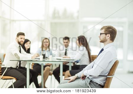 successful Manager sitting in an office chair in the background of the business team and the workplace