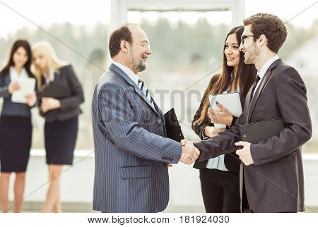 handshake business partners before a business meeting on the background of the office