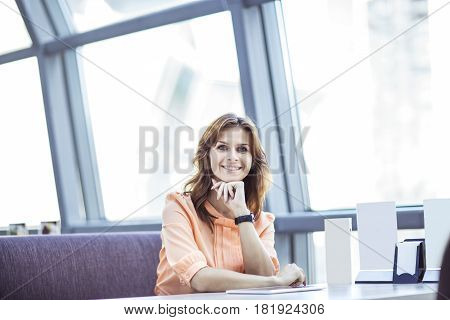 business woman sitting behind a Desk in the spacious office. the photo has a empty space for your text