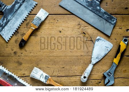 building decoration instruments with paint, brush, palette-knife in builder work on wooden background top view mockup