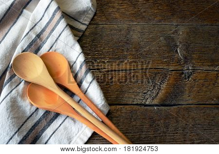 Three wooden mixing spoons on a brown and black stripped dish towel.