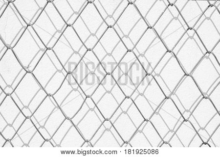Wire mesh and shadow on white concrete wall.