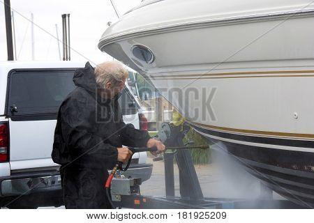Caucasian man pressure washing power boat hull