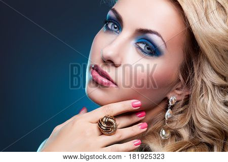 Beautiful blond young woman with bright blue makeup and curly hair wearing turquoise dress. Copy space.