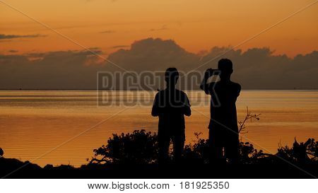 silhouette of people taking photos of the sunset Taking photos of sunsets is a favorite among many, especially in the tropical islands.