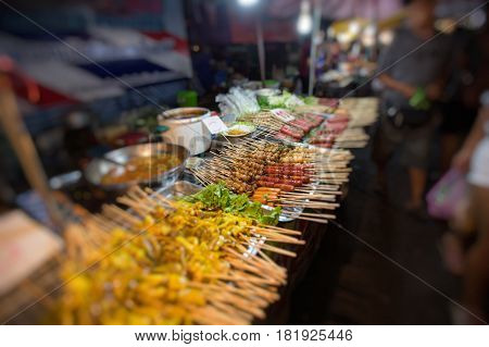 Thai meat ball and sausage with bamboo stick Thai food on street food prepared or cooked food sold by vendorsblurred photo