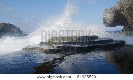 Mesmerizing splash against a stone platform  Giant waves crash against a rocky platform producing beautiful water formations.