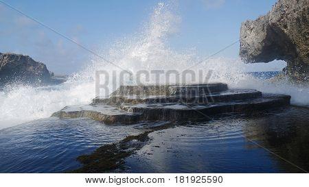 Mesmerizing splash against a stone platform  Giant waves crash against a rocky platform producing beautiful water formations.