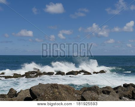 great waves against rocks  white foaming waves crash against rocks creating huge showers