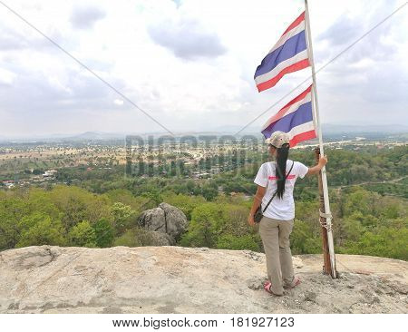 NONG PLA LAI, SARABURI, THAILAND-April 15, 2017. Young woman is standing at the mountain, touching the Thailand flag pole and seeing the scenic.