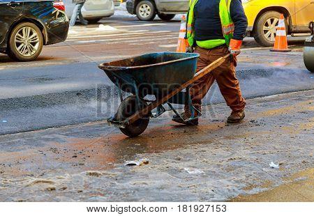 Men Hard Working On Asphalting Road With Shovels